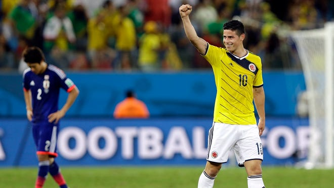 Colombia's James Rodriguez, right, celebrates after scoring his side's fourth goal during the group C World Cup soccer match between Japan and Colombia at the Arena Pantanal in Cuiaba, Brazil, Tuesday, June 24, 2014.
