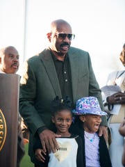 Steve Harvey stands with Jaidin McLemore and Adiva