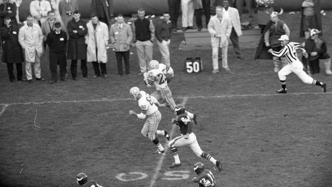 Green Bay Packers halfback Tom Moore (25) heads upfield on a 69-yard run against the Minnesota Vikings at Metropolitan Stadium in Bloomington, Minn., on Oct. 22, 1961.
