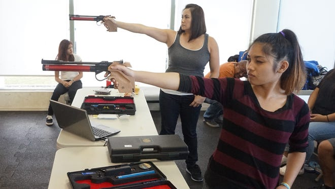 Guam air pistol shooters Hope Delos Reyes, front, and Maria Cenzon prepare for the 2015 Pacific Games by getting in a practice round at LeoPalace Resort on Sunday, June 28, 2015.
