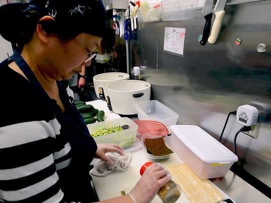 Co-owner Mao Mizushima makes sushi rolls at Shinjuku Station at the corner of North Street and North Winooski Avenue in Burlington.