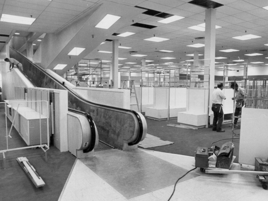 July 22, ,1975: Workers install merchandise racks during