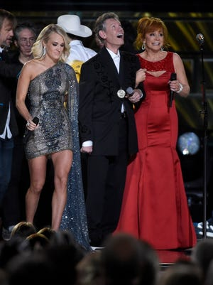 Co-host Carrie Underwood and Reba McEntire onstage with Randy Travis at the 2016 CMA Awards  Wednesday, Nov. 2, 2016, in Nashville, Tenn.