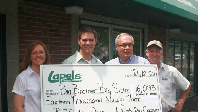 """(Left to right) Lapels Dry Cleaning of Cohasset Franchise Owner Kimberly Wilkinson, Lapels Dry Cleaning CEO Kevin Dubois and Lapels Dry Cleaning of Cohasset Manager Rich Delbou (far right) present the symbolic """"check"""" to Steve Beck, executive director of Big Brother Big Sister Foundation."""