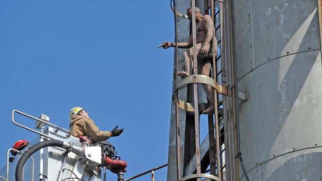 A police detective pleads with a naked man who climbed a tower Thursday at the Vineland Municipal Electric Utility.