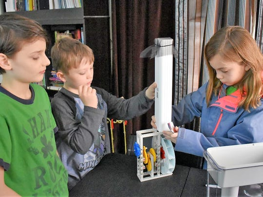 Three members of the Coding Hex team work on an invention. From left, Jack Ireland, Eli Carter and Paige Blair.