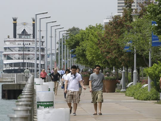 This June 24, 2014 photo shows walkers and joggers along the Detroit RiverWalk in Detroit. Time was when the shores of the Motor City's majestic Detroit River, which separates it from the Canadian city of Windsor, were mostly industrial and uninviting.