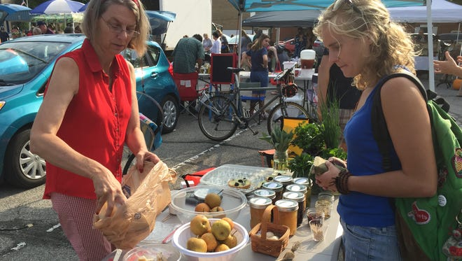 A customer buys Asian pears from a vendor at a past Richmond Farmers Market.