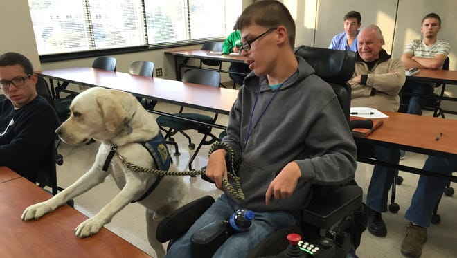 Devin Kirtley has his assistance dog, Ben, display some attention during class Friday at Ivy Tech Community College.