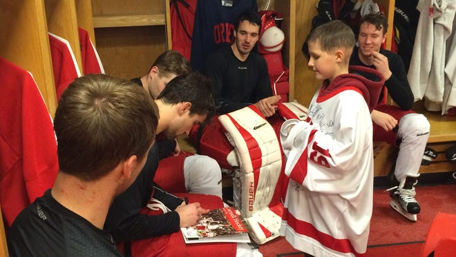 Newark Valley resident Brody Hines, 9, gets autographs from members of the Cornell University men's hockey team in the locker room at Lynah Rink on Tuesday, Nov. 10, 2015