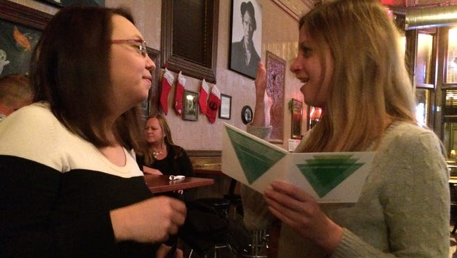 """Jordan Gloyd and Miranda Stringer, two of the six organizers of Wild Bob's Musical Book Club, get a first look at the club's new compilation CD at a holiday party held at Lindberg's Tavern Dec. 1. """"So It Goes"""" will be released to the public at a launch party Dec. 11."""