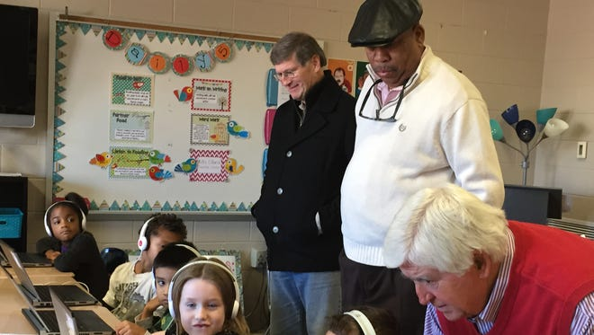 Murfreesboro City Councilmen Bill Shacklett and Ron Washington and Murfreesboro City School Board Chairman Butch Campbell work with first grade students as they tour John Pittard Elementary School on Monday.
