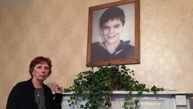 Maureen Aissa stands next to a photo of her son, Jeffrey, who was killed in an arson fire five years ago in Binghamton.