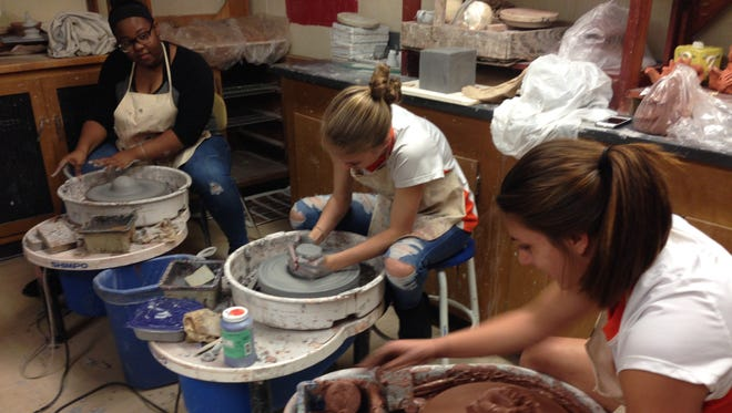 Millville Senior High School students (from left) Zhane Hadden, Kylie Porch and Ashelee Donelson work on their ceramics projects.