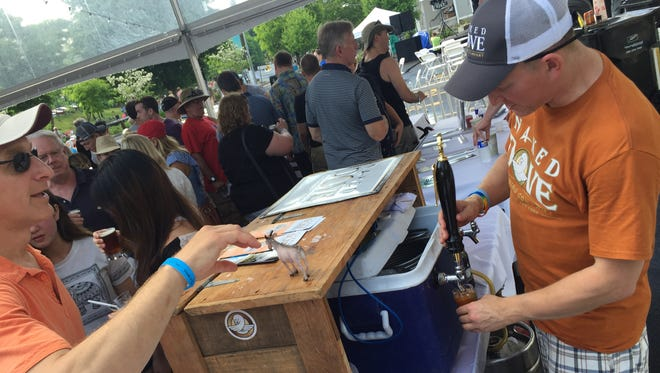Naked Dove Brewing's Chris Schultheis pours a sample of the brewery's Starkers IPA during Pittsford's Paddle and Pour festival on Saturday.
