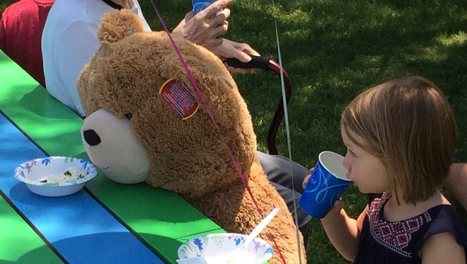 Ella Chernyshov, 3, of Burlington, enjoys a drink while sitting next to her new bear friend Saturday at Vermont Teddy Bear's 35th-anniversary celebration in Shelburne.