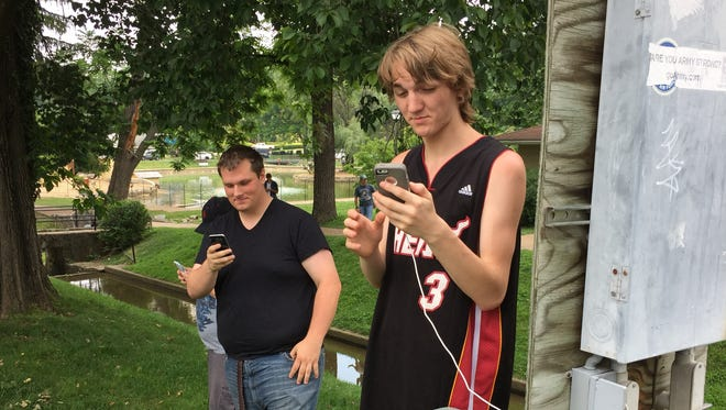 James Davis (right), Sean Feehan (middle) and Kelly Sharkey (right) play Pokémon Go in Gypsy Hill Park on Tuesday afternoon.
