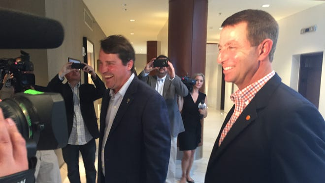 South Carolina coach Will Muschamp (left) greets Clemson coach Dabo Swinney on Tuesday night at the South Carolina Coaches for Charity event in Downtown Greenville
