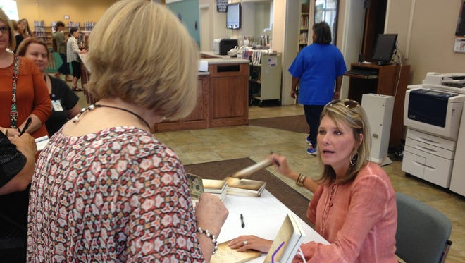 """Susannah B. Lewis autographs a copy of her book, """"Suspicion on Sugar Creek,"""" on Friday at the Jackson-Madison County Library."""