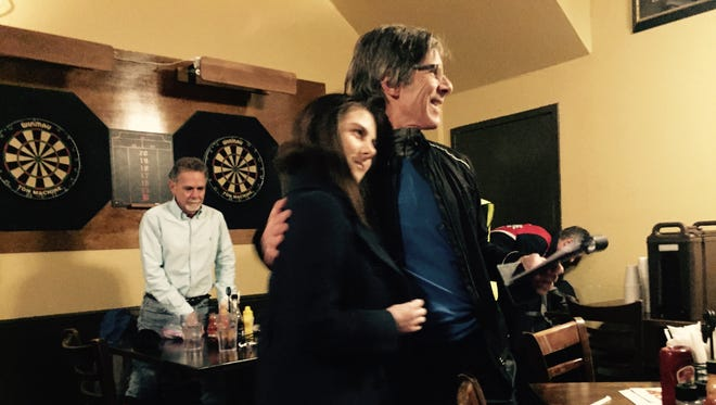 John McCabe and his daughter, Katherine, at Midtown Brewing Co. on Friday. McCabe, a runner, finished his 100,000th mile that night.