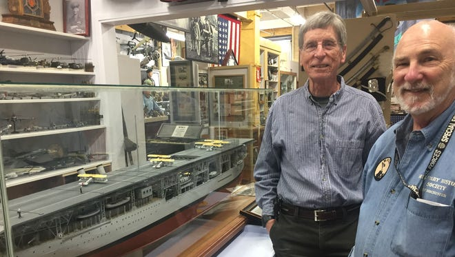 William Emerson, middle, creator of the Langley model, and Chuck Baylis, executive director of the Military History Society of Rochester, standing beside the model of the USS Langley.