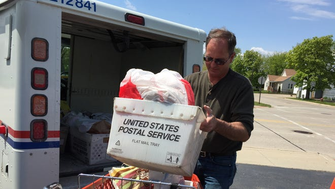 Letter carrier Richard Frink drops off a tote filled with food he collected along his route in North Street as part of the 25th annual Stamp Out Hunger food drive.