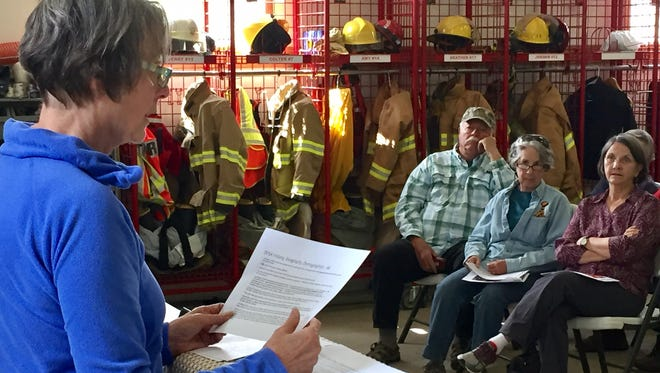 Adrienne Kernaghan, treasurer of the Dearborn Fire Service Area board, reads a proposed fire fee plan during a June 10 meeting at the Dearborn Volunteer Fire Department.