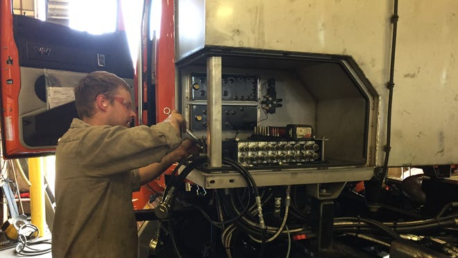 Truck and Trailer Specialties, Inc. employee Jeremy Esch sets pressures in a hydraulic systems of a Saginaw County Road Commission truck at the Genoa Township shop, Friday, June 8, 2018.