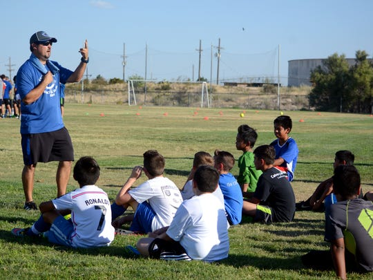 Carlsbad coach Rick Castillo discusses upcoming drills at the Cavemen soccer camp Tuesday at the team's practice field, right across the street from the school's front entrance.