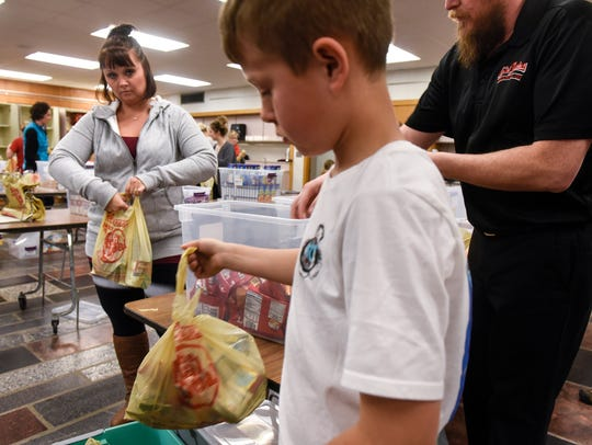 Volunteers gather items to be included in meals as