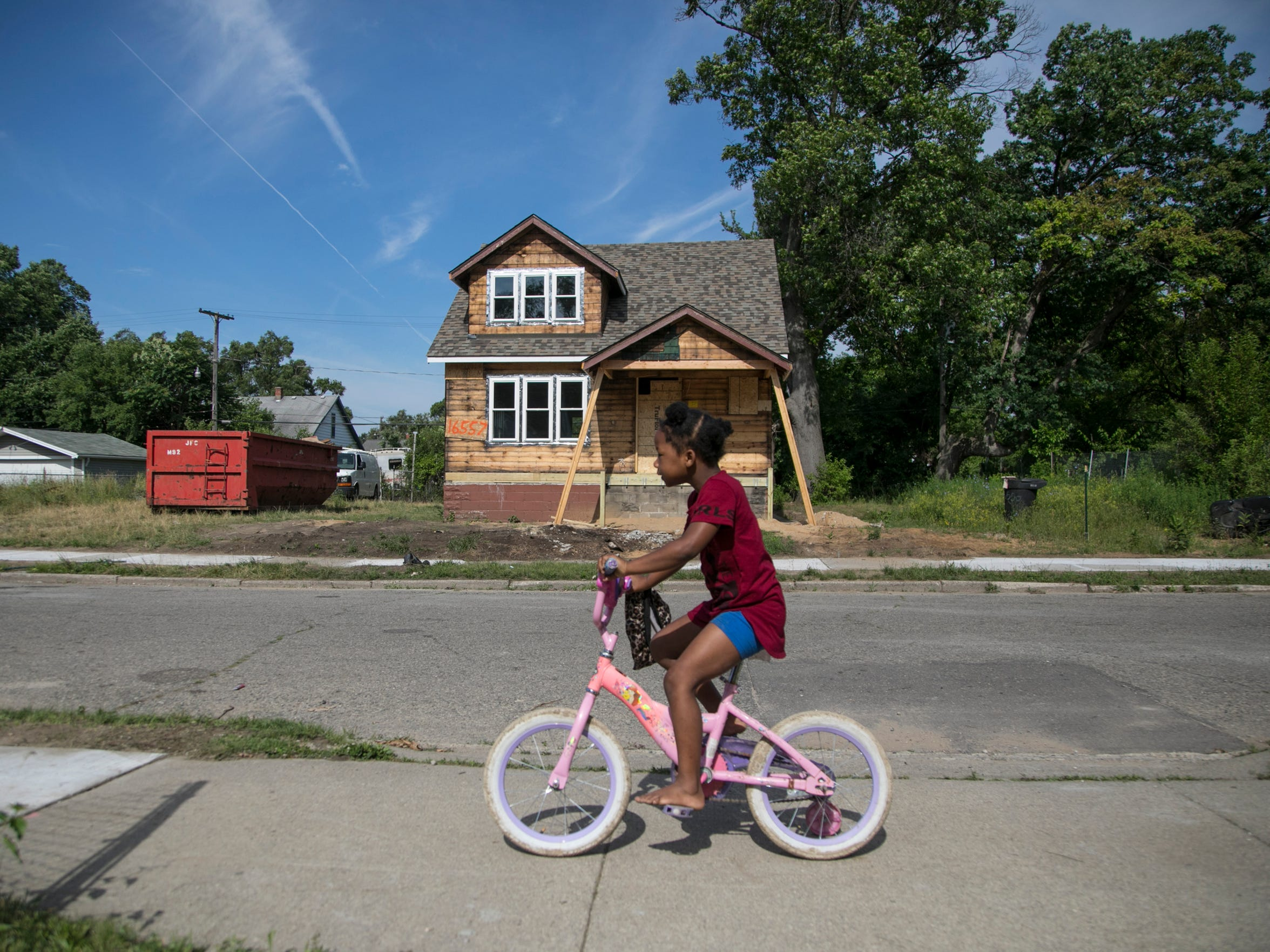Darryona Ivory, 7, rides her bike past a house on San Juan Drive in the Fitzgerald neighborhood on June 25 in Detroit. The house is among three homes now under renovation as part of the Fitzgerald revitalization project. The project's developer is supposed to have 100 homes rehabbed by December 2020.