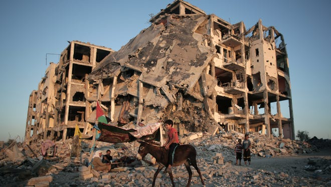 A Palestinian boy rides a donkey next to the destroyed Nada Towers residential neighborhood in the town of Beit Lahiya, northern Gaza Strip.