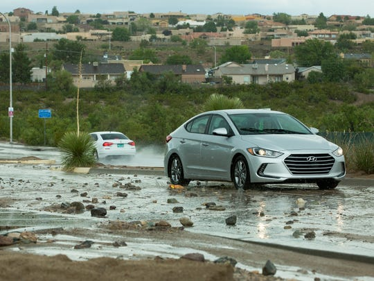Traffic moves cautiously along Roadrunner Parkway on Sunday, July 23, 2017, after water from a downpour moves dirt and large rocks into the roadway.