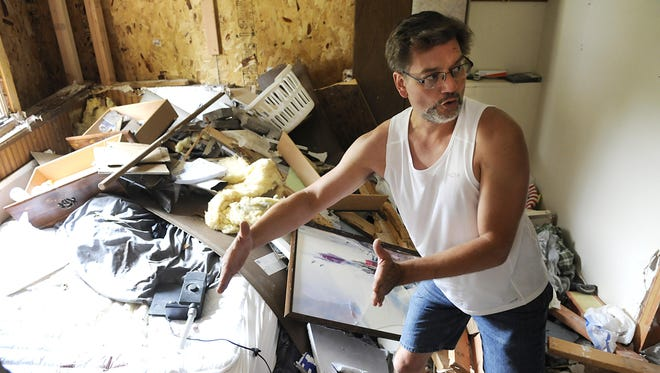 Tom Esplan points out where he was laying at his home in Sauk Rapids about 3:40 a.m. Monday when a pickup crashed into his bedroom while he slept. Esplan had to be extracted from the front window.