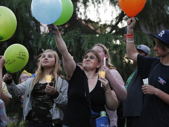 Lisa Gassett, wife of one of the victims of a shooting rampage, lets her balloon go as her son Troy looks on, in honor of her husband, during a candlelight vigil Thursday, April 20, 2017 in Fresno, Calif.