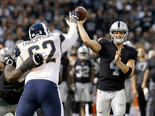 FILE - In this Saturday, Aug. 19, 2017, file photo, Oakland Raiders quarterback Derek Carr (4) passes as Los Angeles Rams defensive tackle Louis Trinca-Pasat (62) defends during the first half of an NFL preseason football game in Oakland, Calif. When Tom Brady, Drew Brees and Aaron Rodgers are ready to move on from the NFL, the quarterback position will still be in good hands. Carr, Marcus Mariota, Jameis Winston, Dak Prescott and Carson Wentz seem on their way to filling big shoes. (AP Photo/Rich Pedroncelli, File)