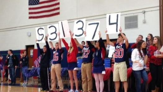 Appleton East Key Club members and football players announce how much money Appleton Tackles Cancer raised during the Homecoming pep rally in September 2014.