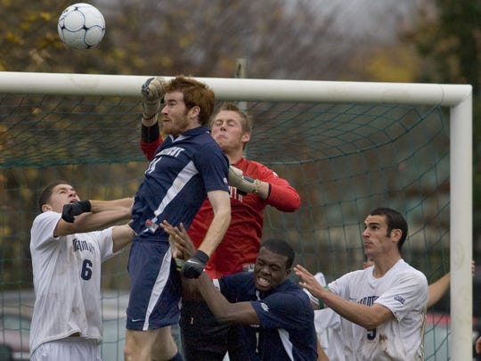 Monmouth University goalie Bryan Meredith punches a ball away from  Connecticut's Robert Brickly during second half action in an NCAA opening round game in 2009.
