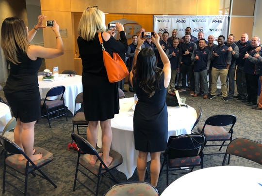 Two wives of UTEP football coaches and a member of the UTEP Marketing Department line up all the new coaches and take pictures of them after UTEP head coach Dana Dimel announced his first recruiting class Wednesday.