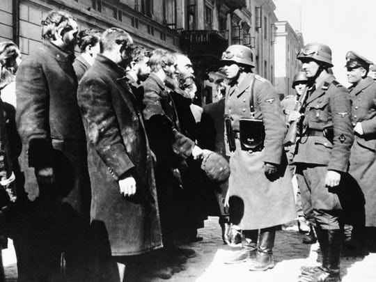 This 1943 file photo shows Nazi officers talking with citizens of the Warsaw ghetto in Poland. An Associated Press investigation found dozens of suspected Nazi war criminals and SS guards collected millions of dollars in Social Security payments after being forced out of the United States.