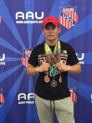 Newark senior wrestler Hunter Thornsberry poses with the three All-American medals he won earlier this month, at the Junior Olympics in Michigan.