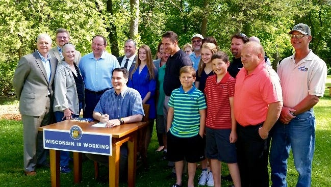 Joining Gov. Scott Walker as he signed the new aquaculture legislation into law, were several members of the Wisconsin Aquaculture Association and their families, along with State Sens. Tom Tiffany and Sheila Harsdorf, and Reps. Mary Felzkowski and Rob Stafsholt.