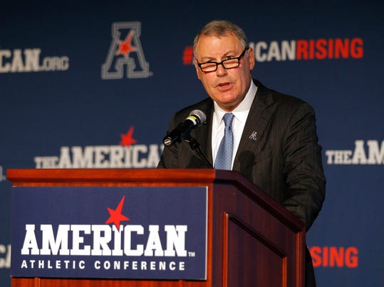 FILE - In this Aug. 4, 2015, file photo, American Athletic Conference Commissioner Mike Aresco addresses the media during an NCAA football media day in Newport, R.I. As Commissioner Mike Aresco continues to push against major college football's glass ceiling, advocating for his schools and trying to position the American Athletic Conference as a Power Five peer, every Tuesday night since Halloween when the CFP rankings are released it becomes apparent just how far off the league is from achieving its goals. (AP Photo/Stew Milne, File)