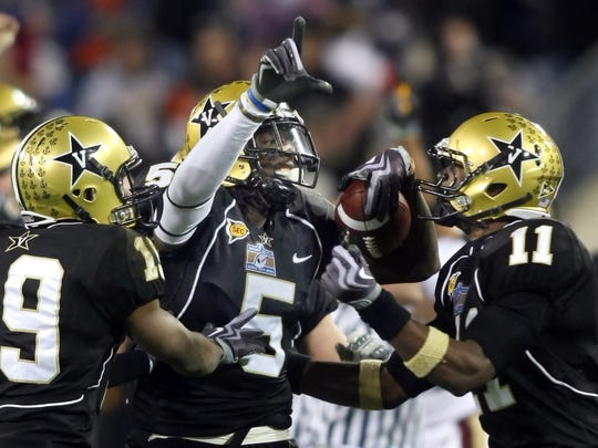 Vanderbilt cornerback Myron Lewis (5) is congratulated by cornerback Casey Hayward (19) and linebacker Brent Trice after intercepting a pass that sealed a 16-14 win over Boston College during the fourth quarter of the Music City Bowl at LP Field in Nashville, on Dec. 31, 2008.