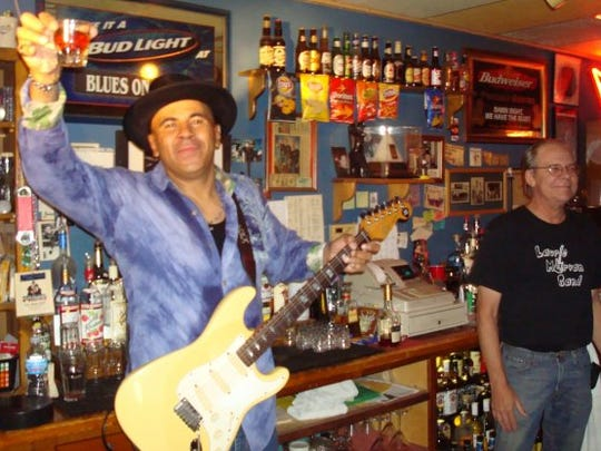 Ronnie Baker Brooks plays behind the bar with Blues on Grand owner Jeff Wagner.