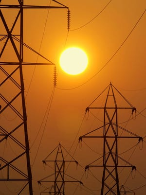 In this Wednesday, Sept. 10, 2003, file photo, the setting sun silhouettes electric transmission lines crossing Berea, Ohio.