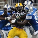 The Lions swarm on Packers RB Eddie Lacy during Sunday's game at Ford Field.