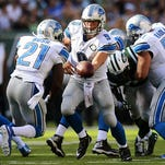 Lions QB Matthew Stafford hands the ball to Reggie Bush during Sunday's win in East Rutherford, N.J.