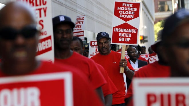 Firefighters gather in front of the federal courthouse in Detroit protesting pension and public safety cuts in July 2013.