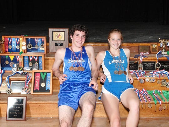 Lamoille Union High School track standouts David Kennedy and Lucy Higgins display the medals and awards they have won over their high school careers. Kennedy set Vermont records in the 200 and 400 meter events and while Higgins set a new mark in the 400 meters at the New England Championships held at Fitchburg,Massachusetts on June 9th.